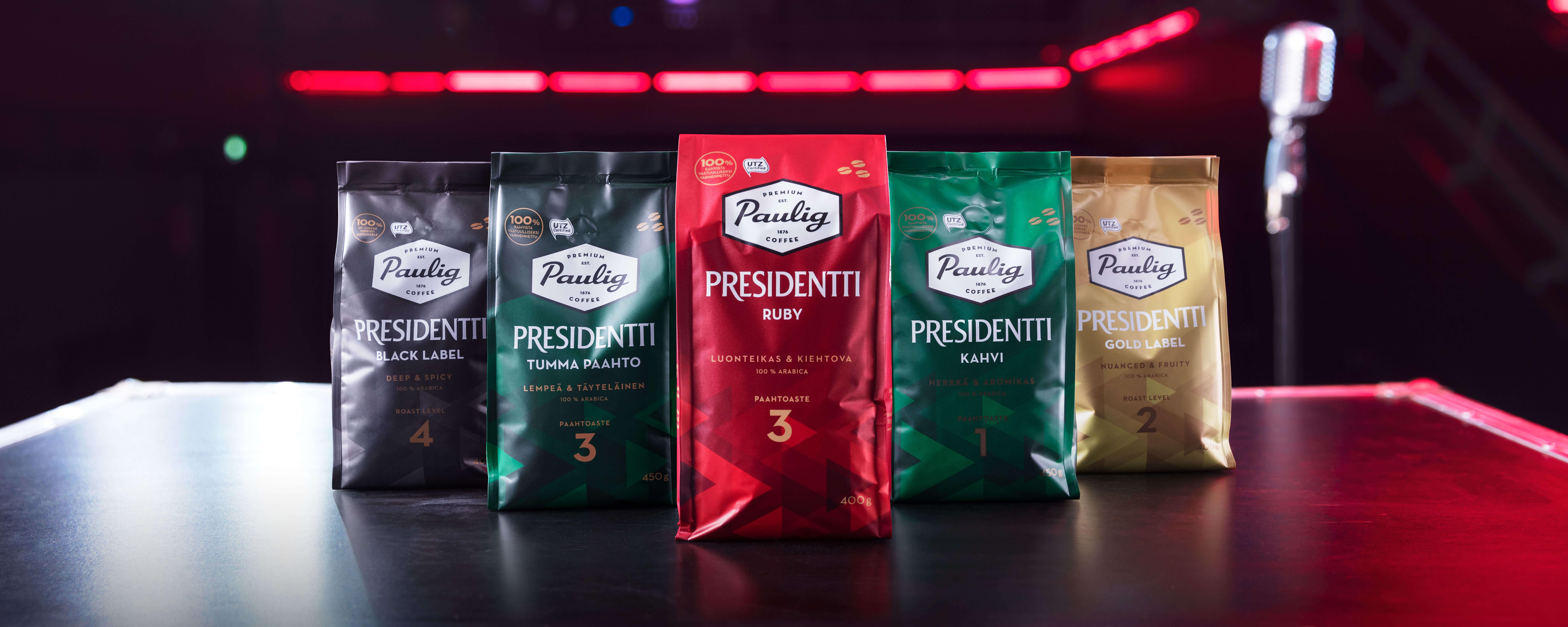Presidentti Ruby kahvipaketteja kuvattuna konserttisalissa tummaa taustaa vasten