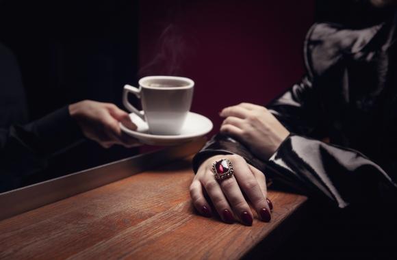 hämärässä valaistuksessa käsi ojentaa valkoisen kahvikupin asiakkaalle jolla on punainen sormus sormessa